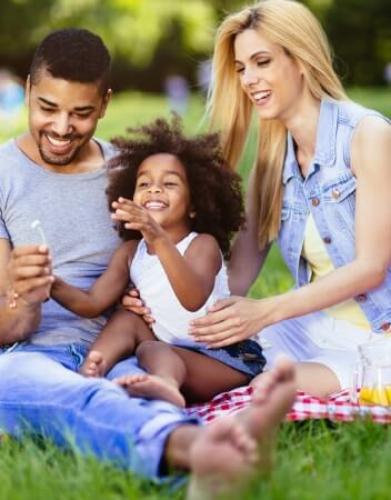 Family of three laughing and playing with dandelions in the park