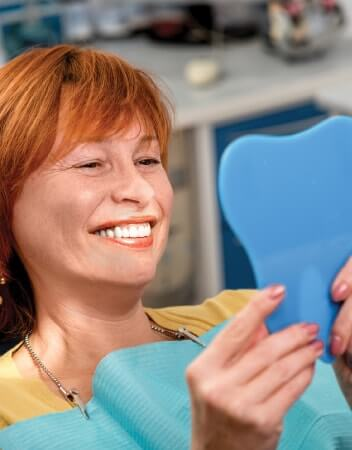 Redhead woman smiling while looking in a mirror at the dentist office