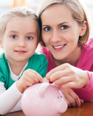 Mother and daughter smiling while putting coins into a piggy bank