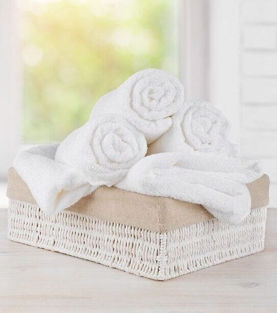 White towels rolled up in a basket on a counter