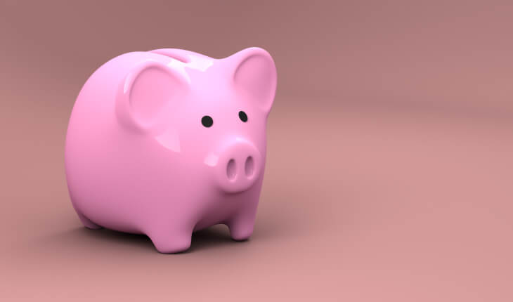 A bright pink plastic piggy bank that stores money stands against a darker pink background