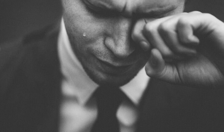 Close-up of a man in a suit looking down while wiping a tear from his eye as he cries due to a painful popping jaw