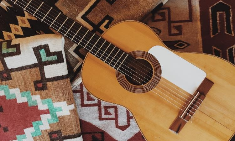 Aerial view of a brown guitar on a stack of Native American blankets