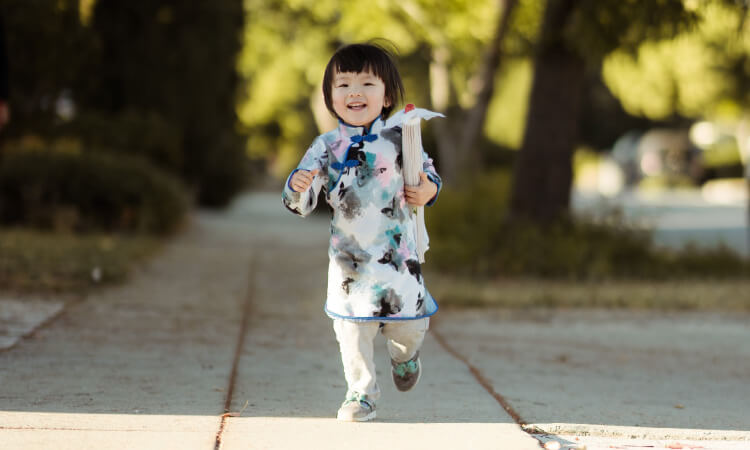 Little girl wearing a white and blue kimono shirt runs along the sidewalk smiling and holding an umbrella