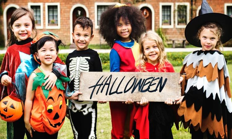 6 smiling children dressed up for Halloween hold a wooden sign that says Halloween