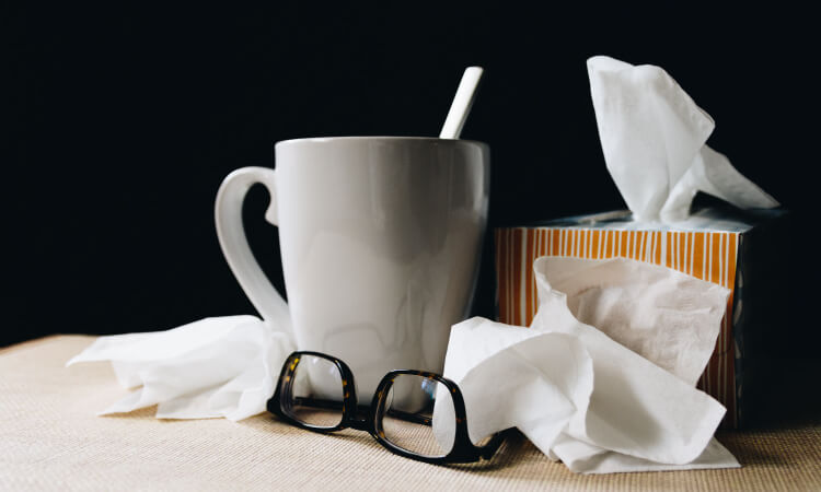 Closeup of a box of tissues, a used tissue, glasses, and a mug because someone is sick with a cold or flu