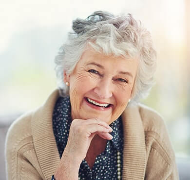 Smiling older woman loving her new dentures