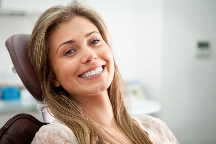 Brunette young woman smiles as she prepares to get her wisdom teeth removed