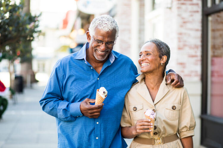 An older husband and wife with dentures smile as they walk down the sidewalk with ice cream cones