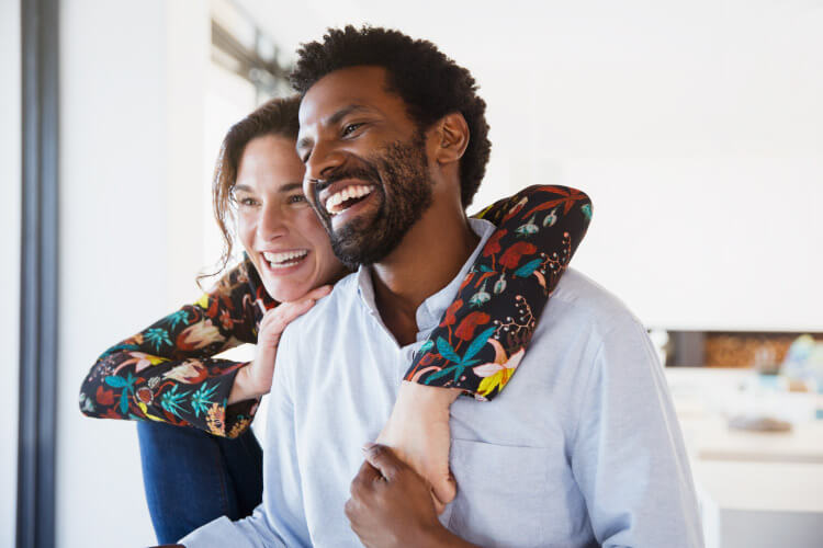 Husband and wife embrace and smile with dental implants in Long Island City, NY