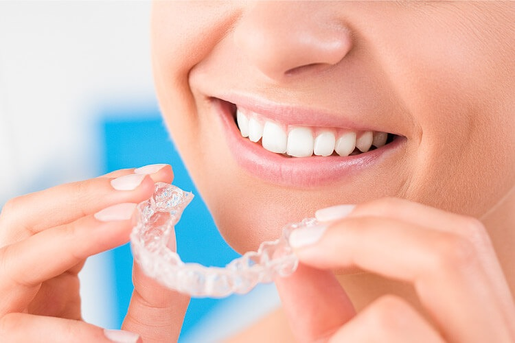 Closeup of woman smiling as she puts in her Invisalign trays to straighten her teeth in Long Island City, NY