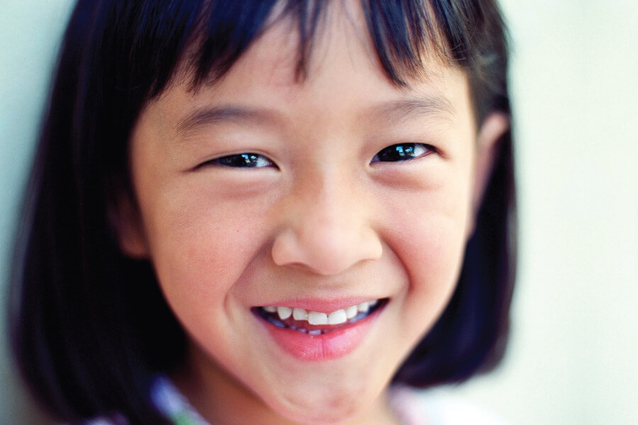 Closeup of a little Asian girl who has overcome her dental anxiety in Long Island City, NY