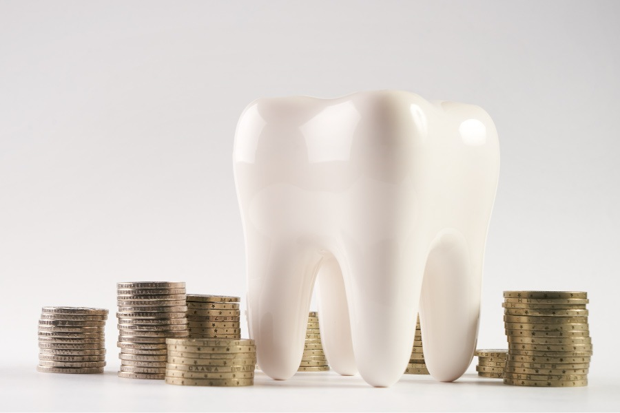 A white tooth surrounded by piles of coins to indicate a Dental Savers Plan vs. Dental Insurance